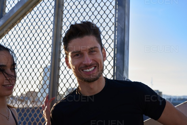 Smiling attractive dark haired man looks at camera stock photo