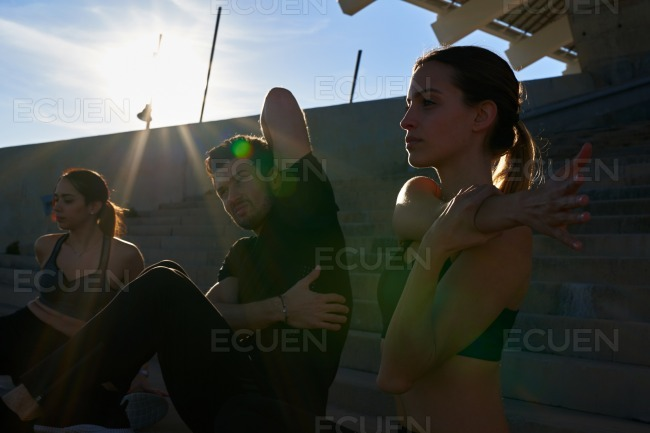 Three young people doing arm stretches outdoors