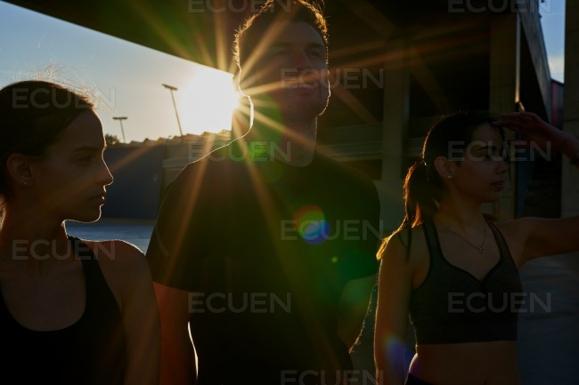 Three young people standing in the sunlight