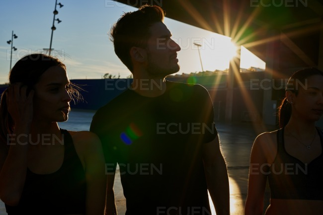 Two young women and young man standing in the sun