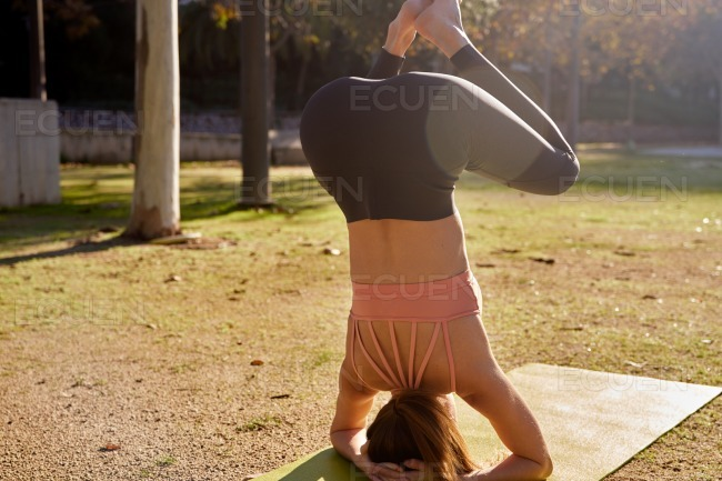 Woman does a pose of the moth yoga pose