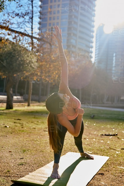 Woman doing a yoga lunge in the park