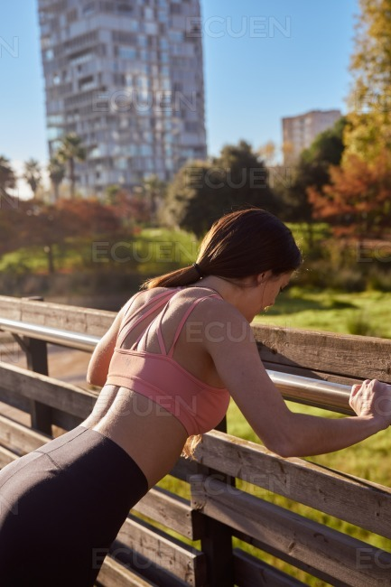 Woman leans facing forward against a barrier stock photo