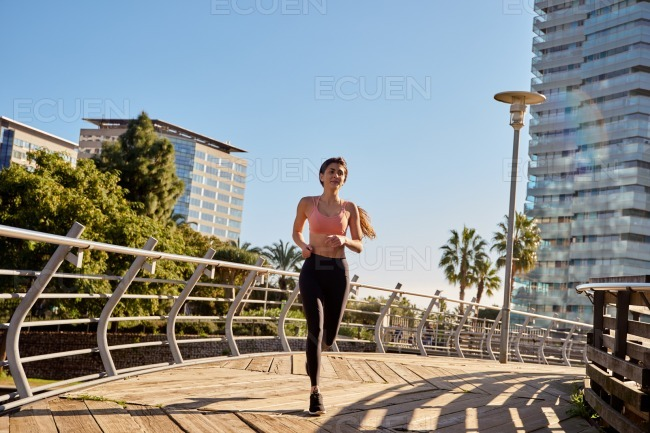 Woman runs on a wooden path with metal railings