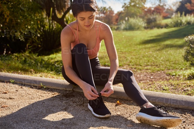 Woman sitting down and tying her shoe lace stock photo