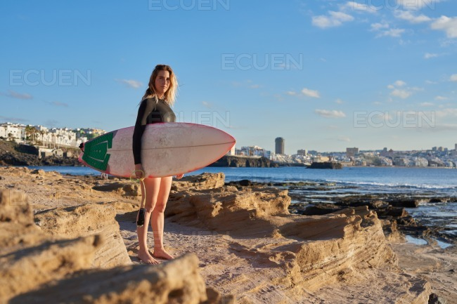 Woman stands on the beach holding a surf board stock photo