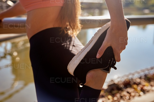 Young woman stretching her leg in the park
