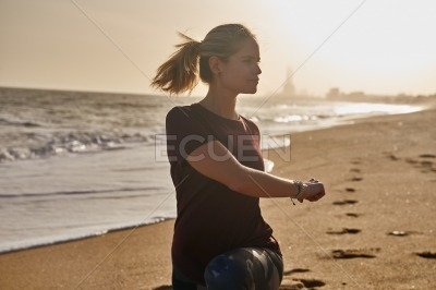 Woman doing a lunge on the beach