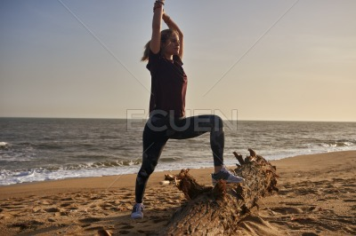 Woman doing stretching exercises on the beach