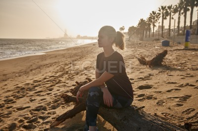 Woman sitting on a piece of driftwood