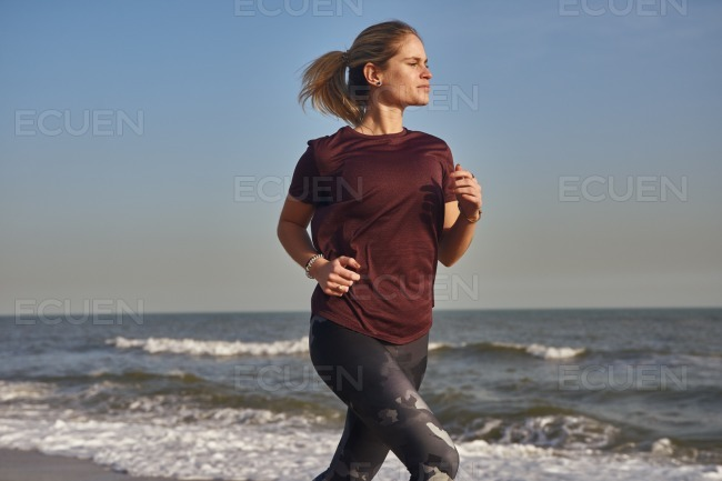 Blonde woman with a pony tail running on the beach