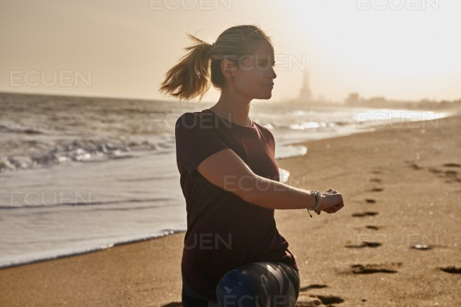 Woman doing a lunge on the beach stock photo