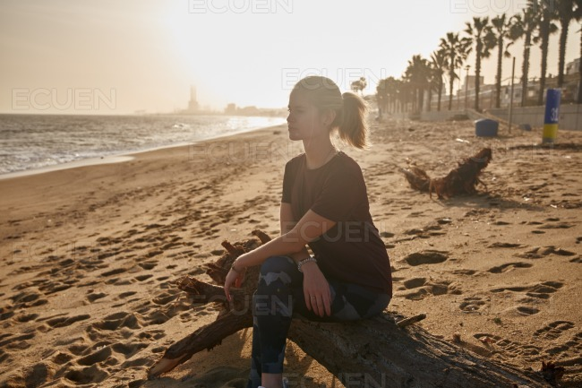 Woman sitting on a piece of driftwood stock photo