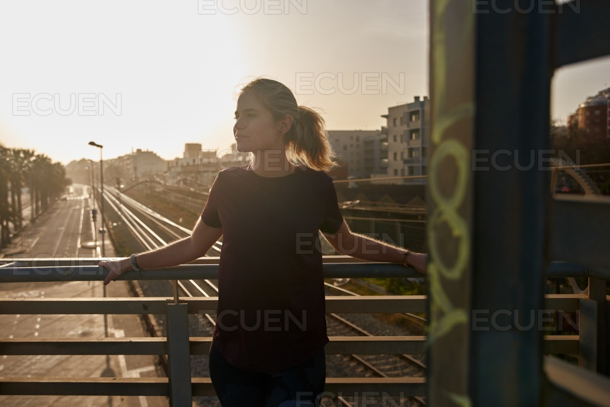 Blond woman leans stands on a railway bridge stock photo