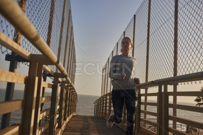Woman jogging near a chain link fence