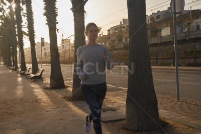 Woman jogging past palm trees on the street