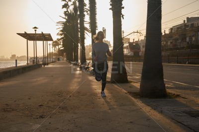 Young woman running on a deserted city street