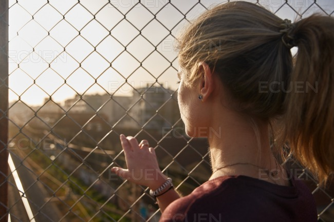Rear view of a woman looking through a fence