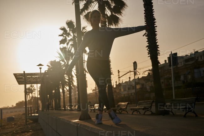 Young woman balances on the kerb stone