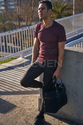 Man holding a sports bag standing in the sun
