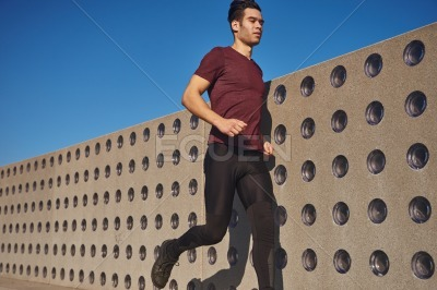 Young man running passed a wall