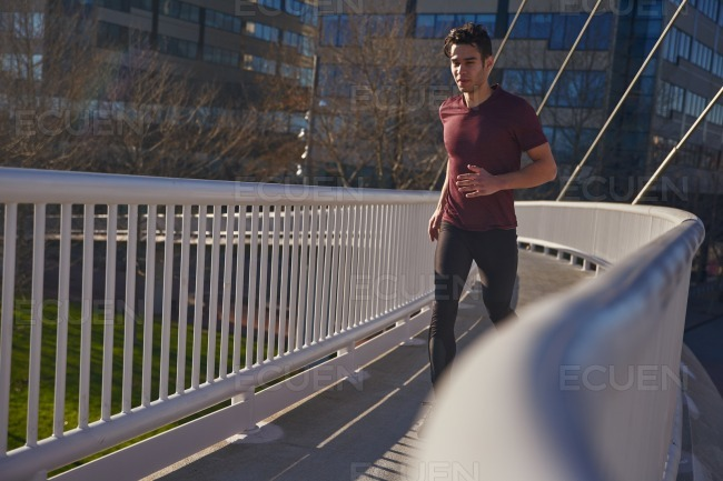 Man jogging along a path on a bridge stock photo