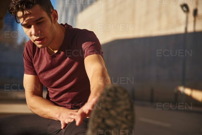 Close up of a man reaching for his feet stock photo