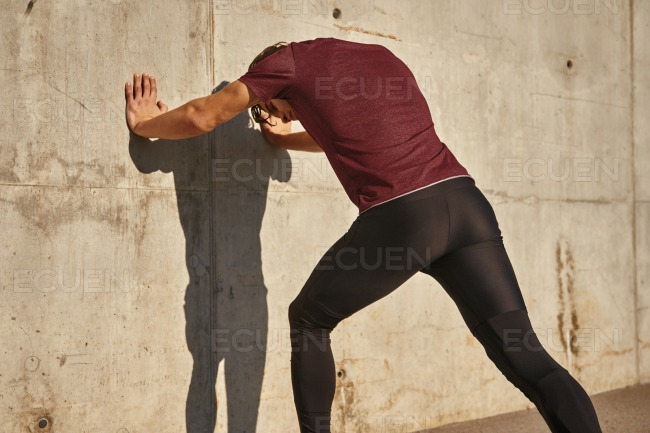 Man pushing against a wall with his hands