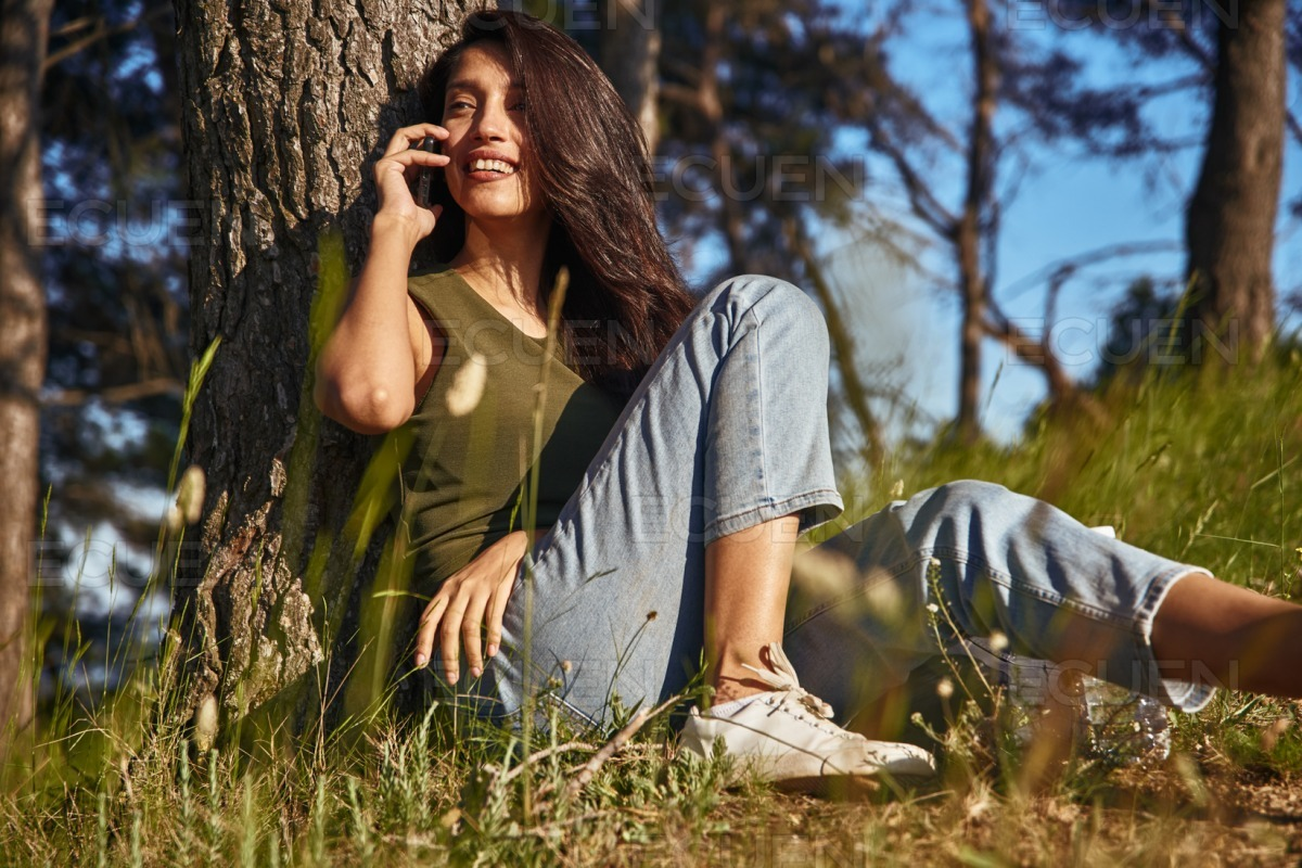 Blissful young lady taking a call outside stock photo