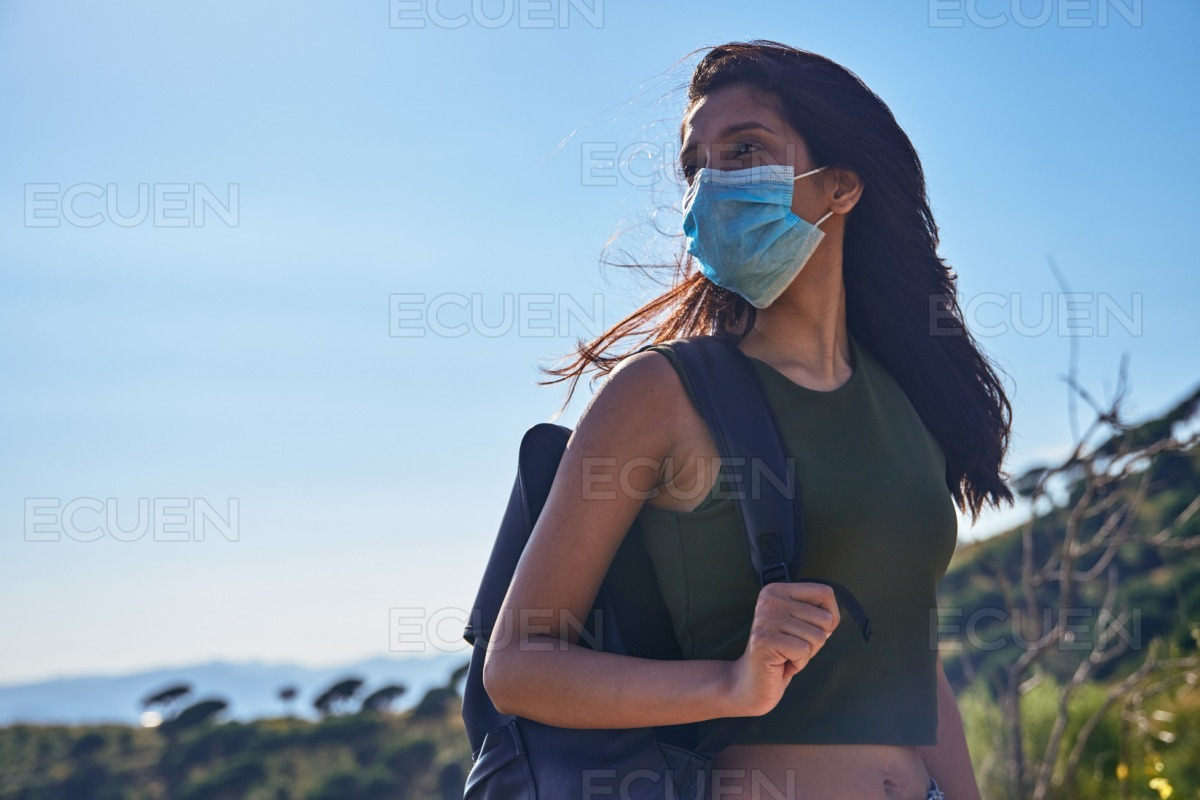 Carefree young lady standing on a hill stock photo