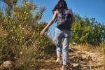 Active young lady taking hike up a hill