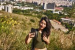 Engaged young lady taking a selfie on a hill
