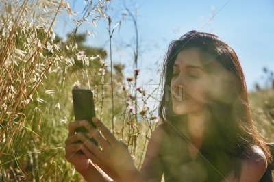 A restful young lady filming while outdoors