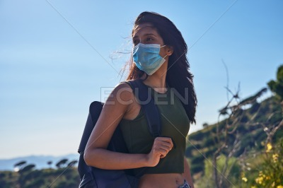 Airy young lady casually standing on a hill