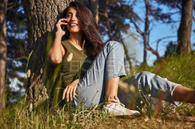 Blissful young lady taking a call outside