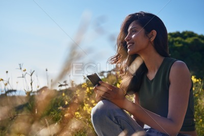 Contented lady sitting on a rock holding her phone