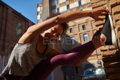 Sporty young woman doing stretch exercises alone