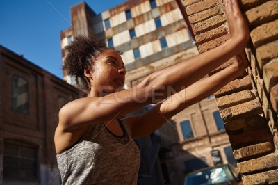Sporty young woman doing wall push ups