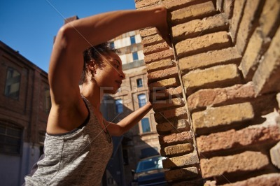 Sporty young woman doing wall push ups in the city