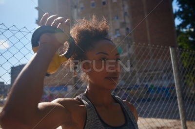 Sporty young woman lifting a dumbbell outdoors