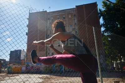 Sporty young woman stretching her body outside