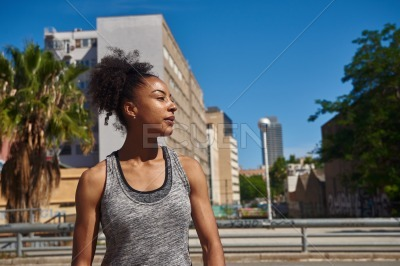 Thoughtful woman in gym clothes standing alone