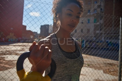 Young black woman holding a dumbbell outdoors
