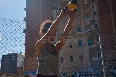 Young ethnic woman working out with a dumbbell