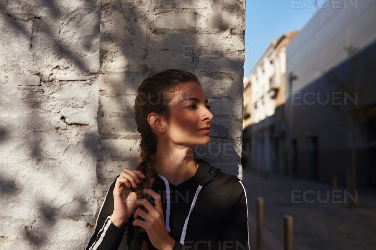 Young woman holds her long plait in her hand stock photo