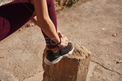 Woman ties the laces of her shoes