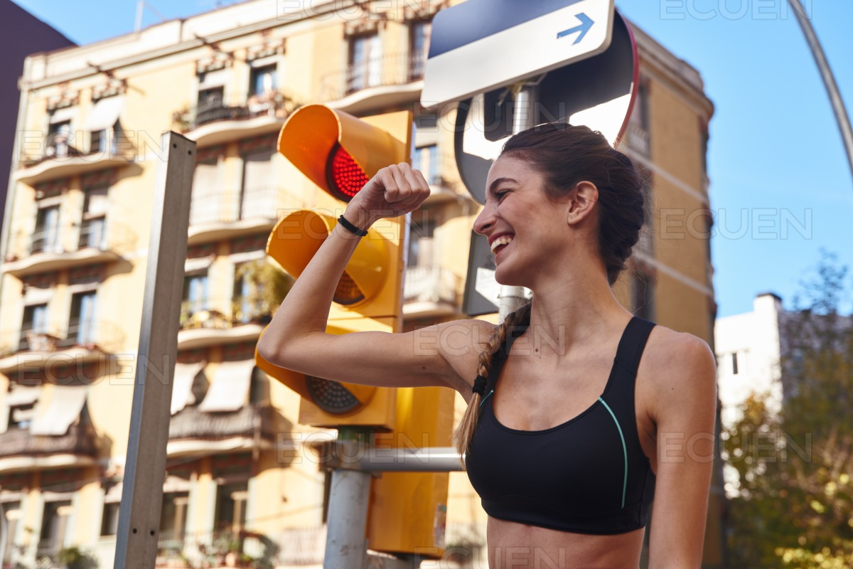 Woman looks down at her flexed arm muscle stock photo