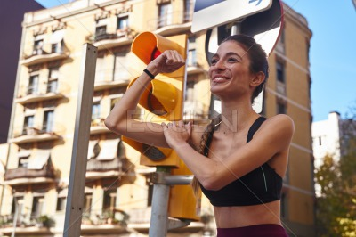 Woman flexes her arm muscles and smiles