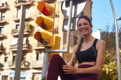 Woman laughing as she poses next to traffic light