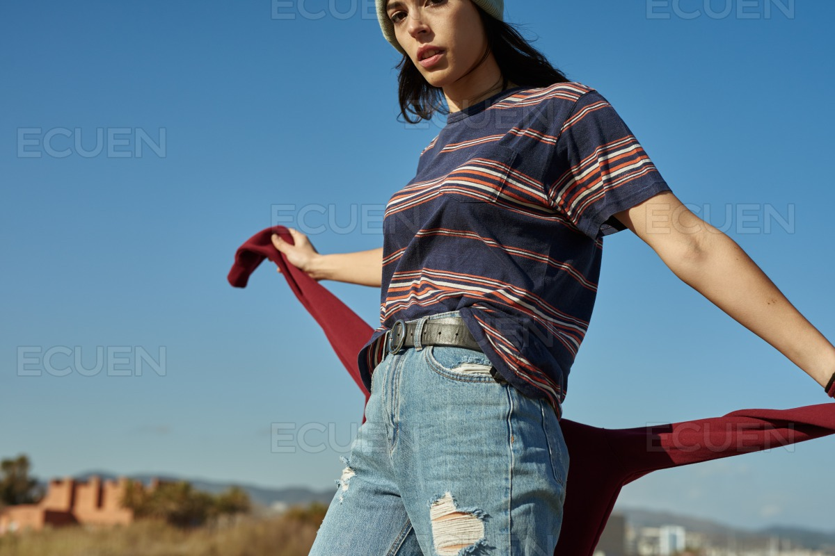 A blase young lady holding on to her sweater stock photo